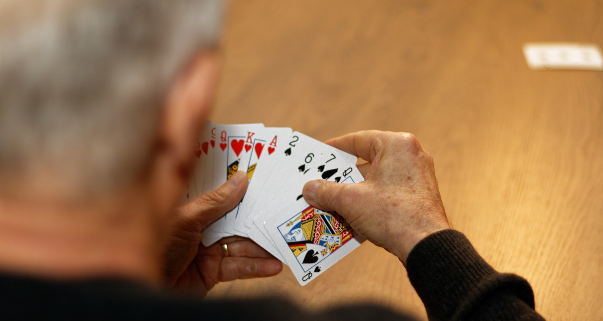 Older gentleman playing cards with friends